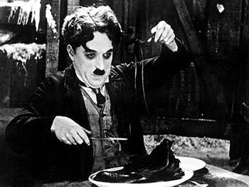 Chaplin comiendo los cordones de las botas como si fueran espaguetis, en una de las escenas más representativas del film