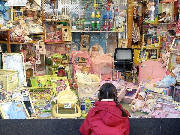 Imagen de archivo: una niña mira un escaparate de juguetes