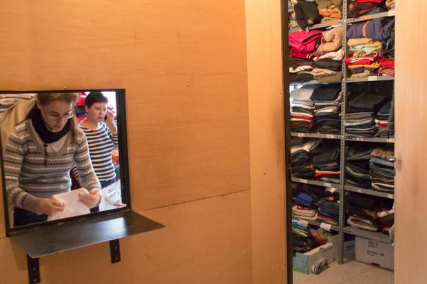 Fotografía: dos voluntarias de Cáritas organizan la ropa que reciben