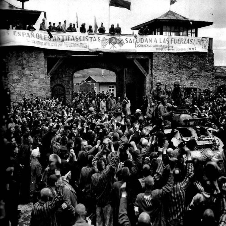 Prisioneros de Mauthausen saludan a la 11ª División Acorazada de los EE UU por su liberación bajo una pancarta escrita en español